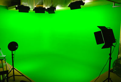Green screen studio cyclorama shown here with lighting packages and film crew off the stage.